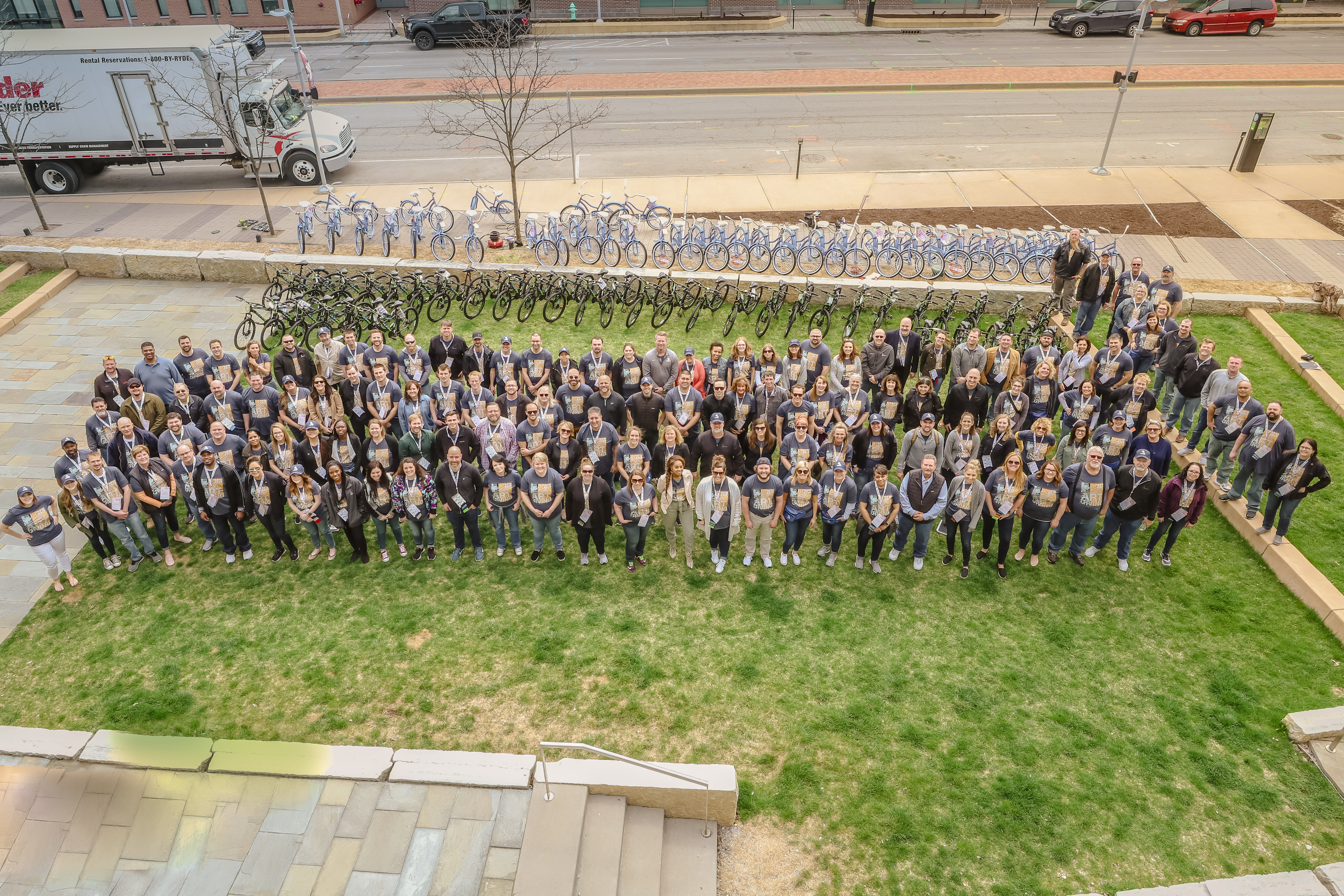 Buckingham Companies employees gathered on lawn near bikes recently built during volunteer project
